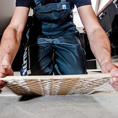 Bilde av en mann som legger gulvfliser