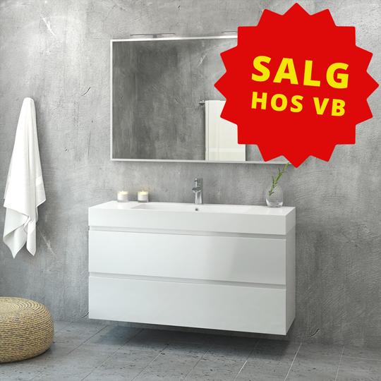 """Et bad med vask, speil og et håndkle. Tekst """"Salg hos VB"""""""